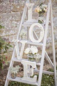 Letras de decoración de bodas acompañadas de obsequios de flores. Vía Pinterest.