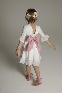 Look de niña para bodas con vestido blanco corto y lazo rosa. Vía Pinterest.
