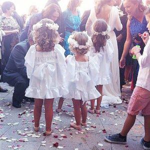 Pequeñas invitadas de boda con vestido blanco y corona de flores a juego. Vía Pinterest.