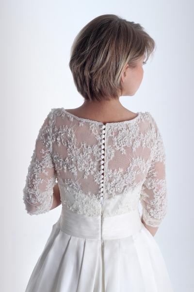 Espalda del vestido de novia en alquiler Cándida de Innovias con talle bordado de encaje y manga francesa