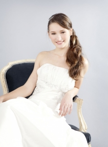 Novia con coleta ondulada ladeada con vestido de Innovias modelo Britta.