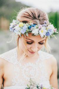 Novia con moño bajo despeinado acompañado de corona de flores