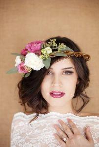 Novia con moño bajo lateral acompañado de una corona de flores. Vía Pinterest.
