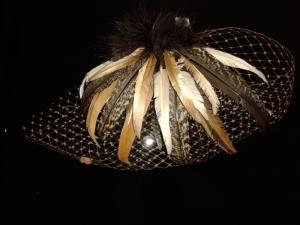 Tocado de novia con plumas en tonos dorados y marrones de Innovias.