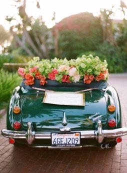 Coche de época descapotable adornado con flores. Vía Pinterest.