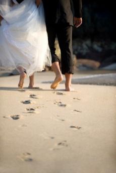 Pareja de novios recién casados paseando por la orilla del mar. Vía Pinterest.