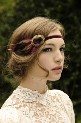 Novia vintage con cinta en tonos berenjena rodeando la cabeza.