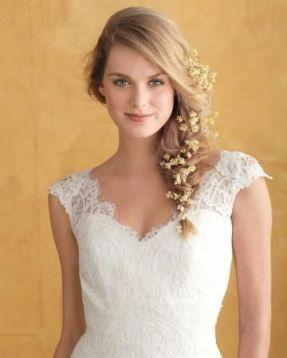 Novia con una trenza ladeada deshecha y pequeñas flores adornando el recogido. Vía Pinterest.