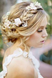 Novia romántica con recogido bajo con trenzas y accesorios de flores para adornar el recogido. Vía Pinterest.