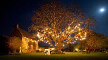 Preciosa finca con un árbol luminoso presidiendo el enlace. Vía Pinterest.