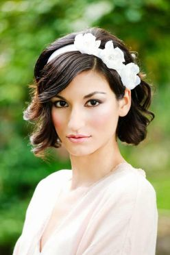 Delicada novia con el pelo corto y ondulado y diadema de flores. Vía Pinterest.