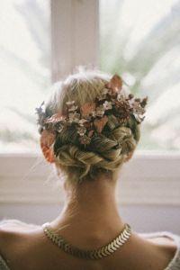 Moño elaborado con trenzas entrelazadas y tocado a base de flores. Vía Pinterest.