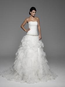 Vestido de novia Innovias modelos Anais con escote palabra de honor, cuerpo drapeado  y falda de volantes confeccionado en organza.