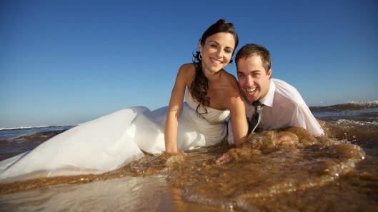 pareja-de-recien-casados-en-la-playa-mientras-las-olas-rompen-sobre-ellos