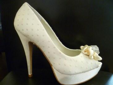 Zapato de novia estilo plumeti coronado con lazo y pedrería.