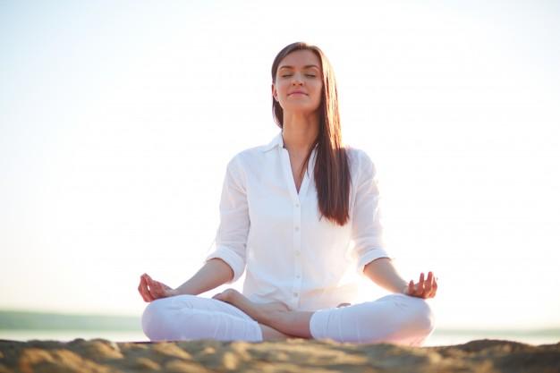 mujer-haciendo-ejercicios-de-yoga-en-la-playa_1098-1449