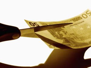 Scissors cutting money --- Image by © Royalty-Free/Corbis