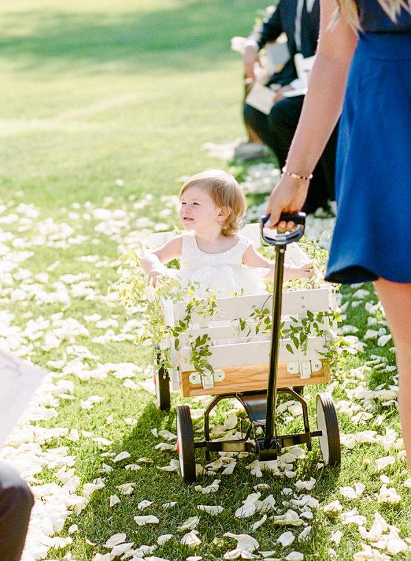 Niña en carrito con una dama de honor. Foto: Rebecca Yale Photography