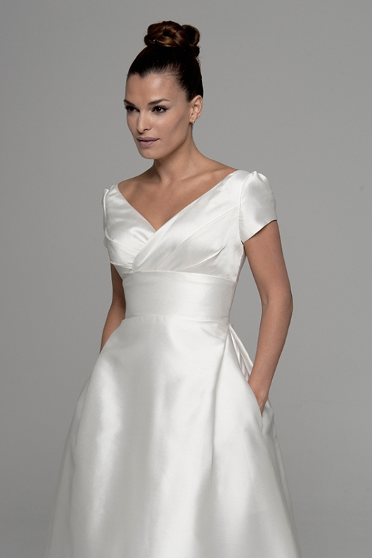 Escote en V del vestido de novia Aline de Innovias de manga corta confeccionado en micado con corte a la cintura y bolsillos