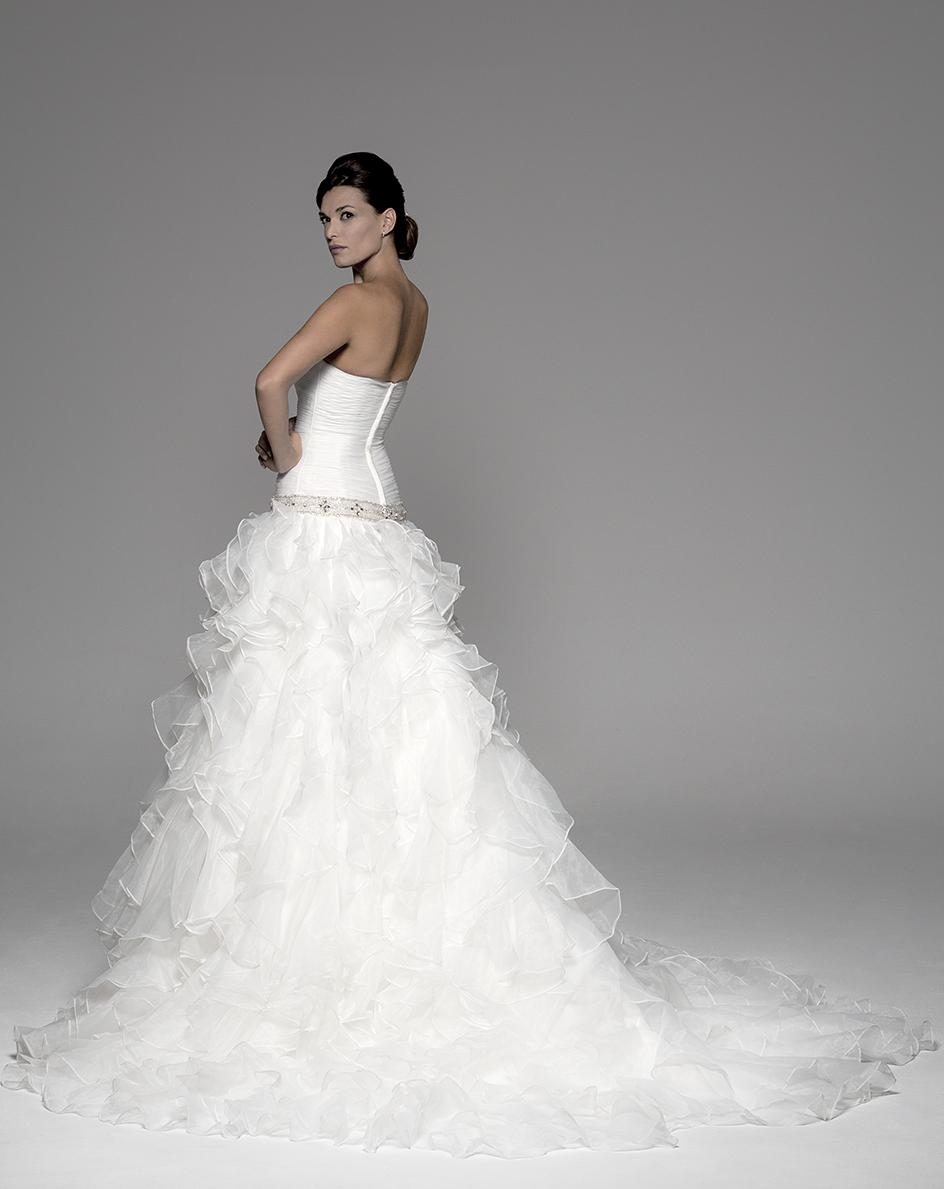 Espalda del vestido de novia Anais de Innovias con cuerpo micro-drapeado ajustado a la cadera, cinturilla de pedrería y falda de volantes